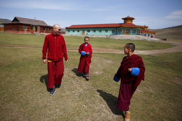 Senior Buddhist monk Lobsang Tayang walks with his students Temuulen (C) and Batkhan Tuul, at the Amarbayasgalant Monastery in the Baruunburen district, Selenge province