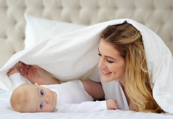 Family portrait of mother and child in white clothes in bed.