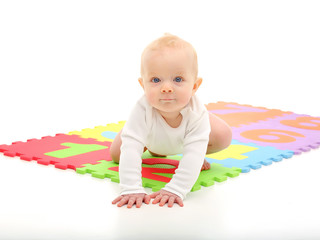 The child creeps on developing a colored Mat.