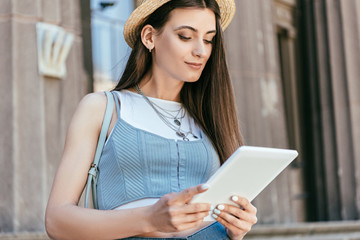 beautiful smiling young woman using digital tablet on street