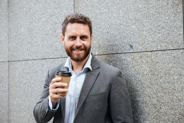 Portrait closeup of bearded handsome man 40s in gray suit and white shirt standing against granite wall, and smiling at camera while drinking takeaway coffee
