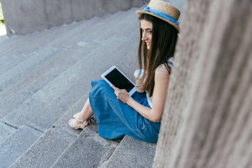 high angle view of smiling girl in hat holding paper cup and using digital tablet while sitting on stairs