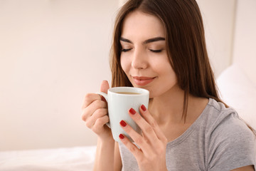Morning of beautiful young woman drinking coffee at home
