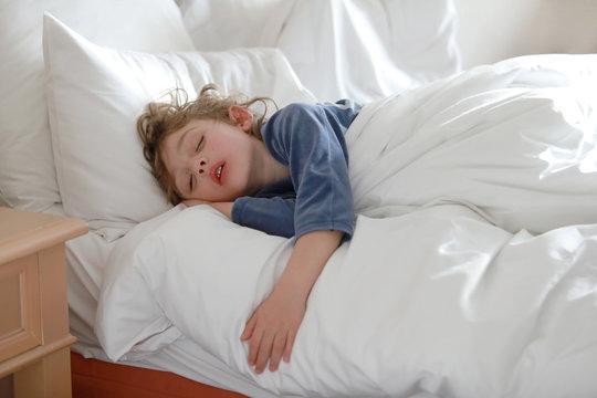 Petit garçon dort paisiblement dans son lit, visage détendu, cheveux longs en bataille sur l'oreiller blanc, bouche légèrement ouverte