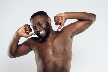 Tired black man with bare chest stretching