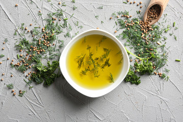Bowl with olive oil and herbs on grey background, top view