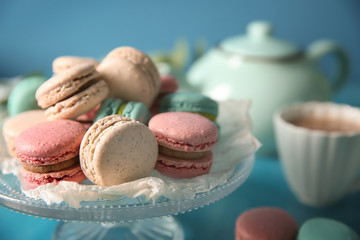 Dessert stand with tasty macarons on table