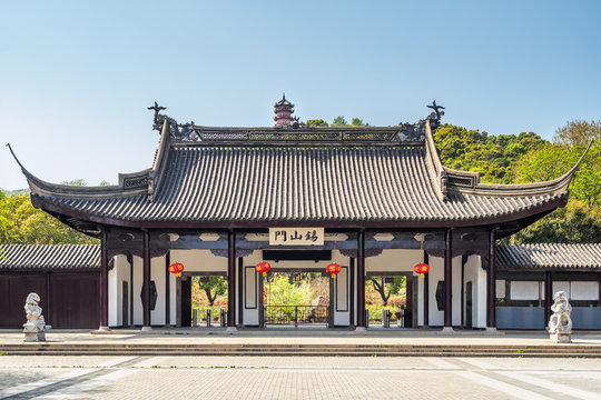 """The main entrance of Xihui Park with the Longguang Pagoda in Wuxi, China. (The translation of the text on the gate means """"tin mountain door."""")"""