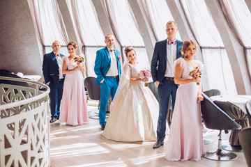 Cheerful and fun groom with bride, bridesmaids with groomsmen posing in hotel reception near large windows. Wedding moment of newlyweds. Bridal day.