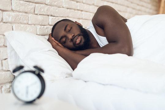 African American man sleeps in bed