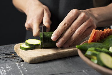 man cutting a zucchini with a knife