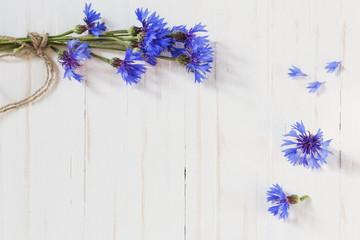 cornflowers on white wooden background