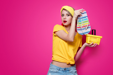 Young redhead girl in yellow t-shirt and blue jeans holding a summer flip flops sandals and supermarket basket on pink background.