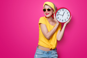 Young redhead girl in yellow t-shirt and blue jeans holding big clock on pink background
