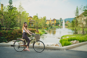 Beautiful woman riding bike in outdoor park, lens flare, nice bicycle path.