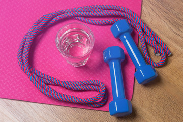 pink mat for fitness or for yoga on the floor, on a dumbbell mat, gymnastic skipping rope and a glass of water, the concept of sport and a healthy lifestyle and water