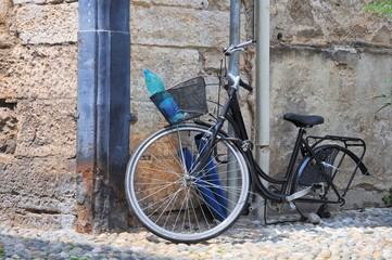 Woman's bicycle tied to a pole and with stolen rear wheel.