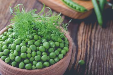 Fresh green peas in wooden bowl, vegan food