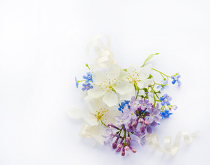 white flowers of apple tree, blue forget me nots, lilac, on white background
