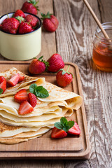 Crepes with fresh strawberries and organic honey for breakfast