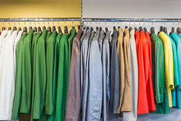 Colorful men's jackets on hangers in a retail shop.