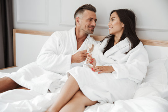 Beautiful couple caucasian man and asian woman wearing white housecoat smiling to each other and drinking sparkling wine from glasses, while lying in bed at hotel room