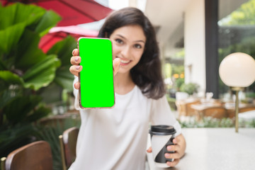 young woman showing modern gold smartphone with green screen for replacement