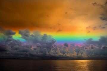 sunset sky rainbow over silhouette orange cloud on the sea
