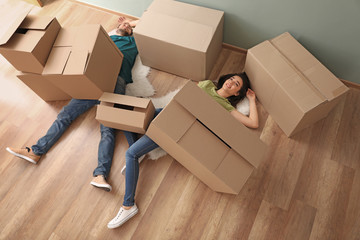 Young couple buried under heap of boxes indoors. Moving into new house