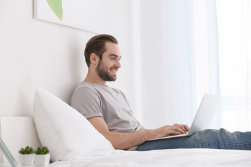 Male freelancer working with laptop in bed
