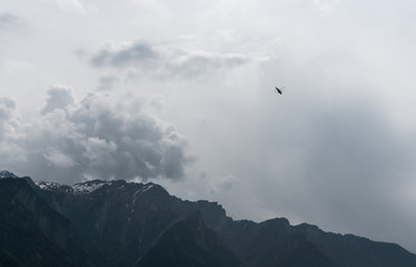 rescue helicopter fliying over mountains into a dark and stormy ominous sky