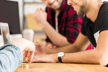 Cropped photo of friends sitting at a table and playing with golden coins