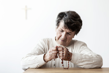 Sad and lonely grandmother with rosary praying to god in the church
