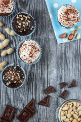Tasty chocolate cupcakes on a grey wooden background with chocolate and nuts