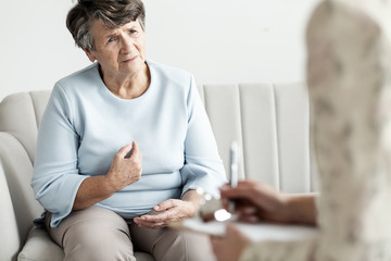 Worried grandmother talking with financial advisor about debts