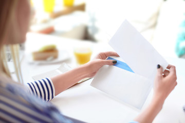 Young woman putting letter into envelope at table in cafe. Mail delivery Wall mural