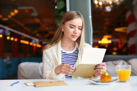 Young woman reading letter at table in cafe. Mail delivery