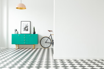 Empty wall and turquoise cabinet with decorations standing next to a bike in a hallway interior with checkered floor. Place for your poster or furniture