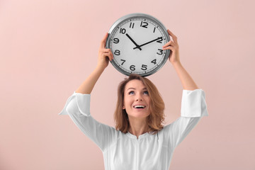 Mature woman with clock on color background. Time management concept