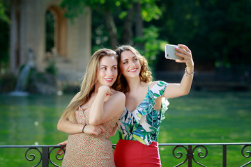 Girls smile and take a selfie together. Two girls take a selfie together and smile. In the background the green lake in the outdoor park.