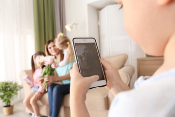 Little boy taking photo of his cute little sisters and mother at home