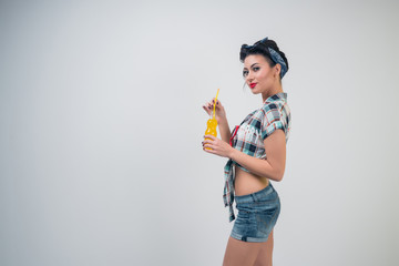 A beautiful girl drinks a soda. Style pin up. Fashion.