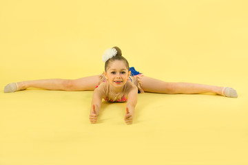 beautiful young girl engaged in gymnastics on a yellow background