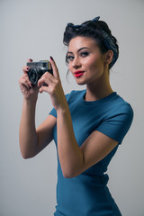 Sexy girl in pin-up style makes the photo on the retro camera