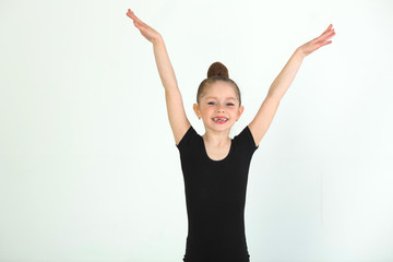 beautiful young girl engaged in gymnastics on a white background in a black suit
