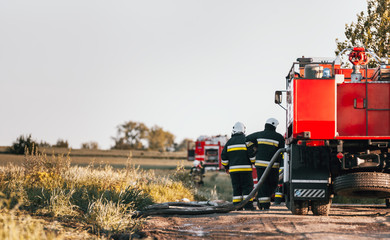 Firefighters near fire truck preparing to extinguish fire among the fields