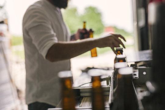 Mid section of brewery worker preparing beer bottles