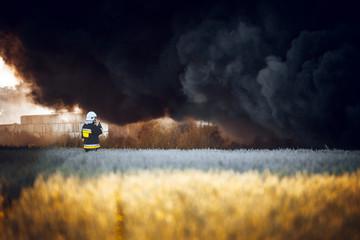 Firefighter in field standing in front of dark smoke from fire