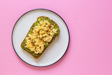 Egg on whole wheat bread with avocado, pink background top view
