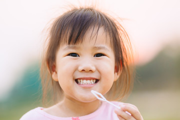 3 years old kid smiles widely and show her teeth : Close up picture.